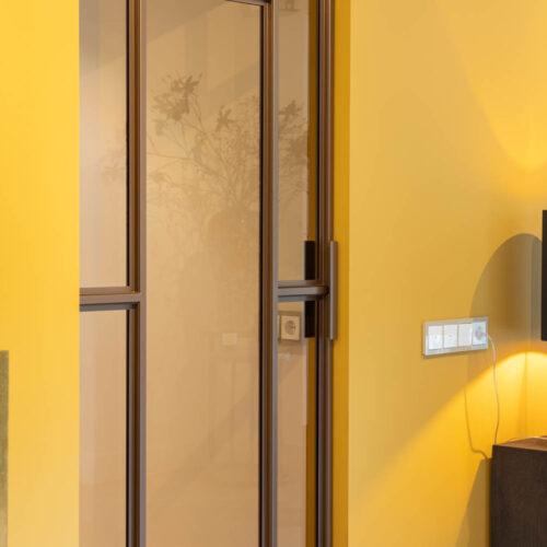 Bronzen stalen deur in kleurrijke woning enkele stalen deur
