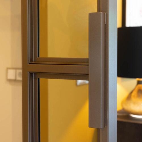 Bronzen stalen deur in kleurrijke woning handgreep detail