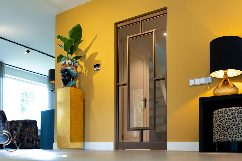 Bronzen stalen deur in kleurrijke woning taatsdeur
